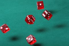 Bouncing dice. Dices being thrown in a craps game, or yatzee or any kind of dice involved game, Dices are a clear red color on a green felt table Royalty Free Stock Images