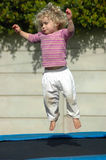 Bouncing kid. A cute little caucasian blond girl child jumping on a trampoline in the backyard outdoors Royalty Free Stock Photo