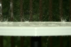 Bouncing water on table. Bouncing raindrops on white table Stock Photography