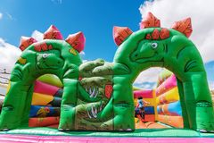 Bouncy castle in the shape of dinosaurs in a children`s playground outdoors