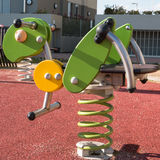 Bouncy colorful spring playground equipment, plastic grasshopper. Bouncy colorful spring playground equipment in public park, plastic grasshopper on springs Royalty Free Stock Images
