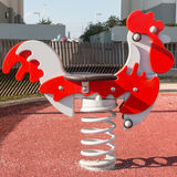 Bouncy colorful spring playground equipment; plastic rooster on. Bouncy colorful spring playground equipment in public park, plastic cock on springs Stock Photos