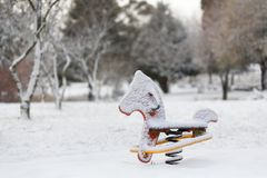 Playground equipment rocking horse covered in snow stock photography