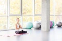Bound Angle, lotus posture. Woman doing yoga, looking at camera. Studio shot Royalty Free Stock Images