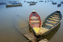 Bound boats in contrary colors. Three old boats, bound together, with weathered, contrary color on them. The colorless one is sunken, and has swimming fishes in Royalty Free Stock Images