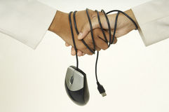 Bound Handshake. Two women shake hands and their wrists are bound by a mouse cable Royalty Free Stock Photo