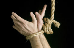 Bound and Struggling. Hands of a caucasian male tied together with a long rope with fingers spread wide as if struggling to get free Stock Photos