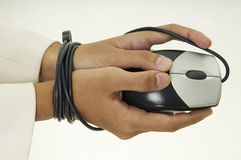 Bound By Technology 3. A woman holds a mouse and her hands are bound by the cable Stock Photography