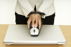 Bound By Technology 5. A woman holds a mouse over a laptop computer, her hands are tied up by the mouse cable Stock Images