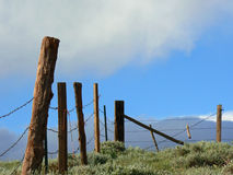 Boundaries. Barb wire fence at the top of a hill with blue sky and clouds in background Royalty Free Stock Image