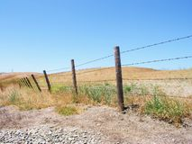 Boundaries. Old barbed wire fence out in the country Stock Photos