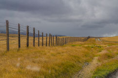 The boundary of a wooden fence with barbed wire and clouds Royalty Free Stock Images