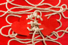 Bounding love. Two hearts bound together with white thread on red background Stock Photography