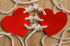Bounding love. Two hearts bound together with white thread on red background Stock Image