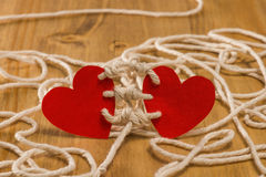 Bounding love. Two hearts bound together with white thread on red background Stock Images