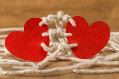 Bounding love. Two hearts bound together with white thread on wooden background Stock Photography