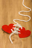 Bounding love. Two hearts bound together with white thread on wooden background Stock Images