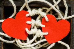 Bounding love. Two red paper harts bounded to together with white thread on a wood chest Stock Image