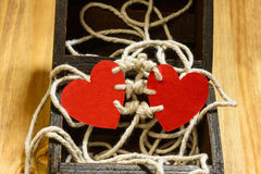 Bounding love. Two red paper harts bounded to together with white thread on a wood chest Stock Photos