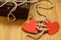 Bounding love. Two red paper harts bounded together with white thread and wood chest on wooden background Stock Photography