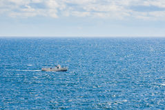 Boundless blue sea and lonely ship Stock Images