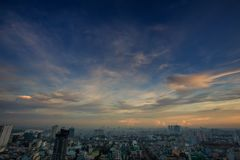Boundless Blue Sky with Sunlight behind Clouds above City. Boundless blue sky and sunlight behind clouds above modern city skyscrapers at sunset in Saigon Royalty Free Stock Image