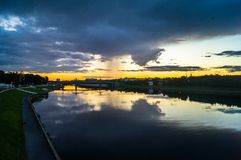 Mesmerizing blazing sunset over the mirror glossy surface of the Volga river, reflecting dramatic sky. City of Tver, Russia. Boundless expanse. Mesmerizing Stock Photo