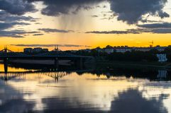 Mesmerizing blazing sunset over the mirror glossy surface of the Volga river, reflecting dramatic sky. City of Tver, Russia. Boundless expanse. Mesmerizing Stock Image