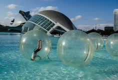 The boundless joy of childhood. A boy is somersaulting in a bubble floating in the water. In the background is the City of the Arts and the Sciencesof Santiago Stock Photography