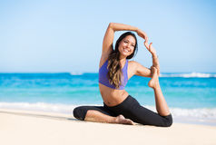 Boung woman in yoga pose at the beach. Beautiful young woman in yoga pose at the beach. Morning zen mediation outdoors. Practicing yoga. Healthy Active Lifestyle Stock Photos