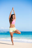 Boung woman in yoga pose at the beach Stock Image