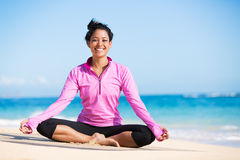 Boung woman in yoga pose at the beach. Beautiful young woman in yoga pose at the beach. Morning zen mediation outdoors. Practicing yoga. Healthy lifestyle Royalty Free Stock Photos