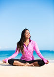 Boung woman in yoga pose at the beach. Beautiful young woman in yoga pose at the beach. Morning zen mediation outdoors. Practicing yoga. Healthy lifestyle Royalty Free Stock Images