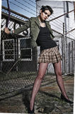 Bounty escape. Young retro girl against barbed wire fence Stock Photography