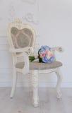 Bouqet azul de la flor que miente en la silla antigua blanca Fotos de archivo libres de regalías