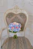 Bouqet azul y púrpura de la flor que miente en la silla antigua blanca Imagen de archivo