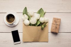 Bouqet of white tulips and gift box on wooden background. White tulips on wooden background. Creative bouqet in envelope, gift box, coffee, smartphone. Mothers stock photos