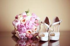 bouquest的牡丹和一个对妇女鞋子 免版税库存图片