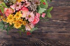 Bouquet étonnant d'automne avec les baies et la pomme sur le backgrou en bois Photographie stock