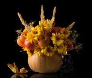 Bouquet of apples, flowers and dried plants in vase from pumpkin next to candle is burning, isolated on black. Background Stock Image