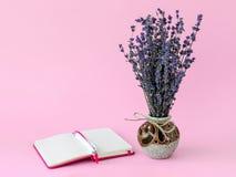 Bouquet aromatique de lavande sèche dans un beau vase en céramique et de stylo bille blanc sur le bloc-notes de papier rayé ouver images libres de droits