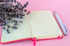 Bouquet aromatique de lavande sèche sur un bloc-notes de papier rayé ouvert ouvert dans une couverture rose et de stylo bille bla image libre de droits