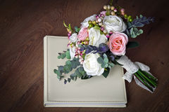 A bouquet of artificial flowers lies on the wedding photo book 1 Stock Photos
