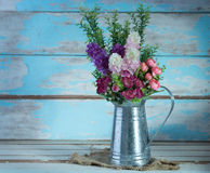 A bouquet of artificial rose flowers in galvanize can set on ret Royalty Free Stock Photography