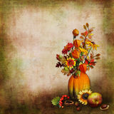 Bouquet of autumn leaves and flowers in a vase from a pumpkin on an isolated background. Vase from a pumpkin with autumn leaves and flowers on a white background Stock Photography