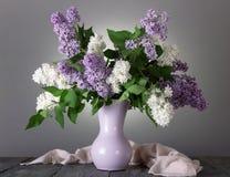 Bouquet avec du charme des fleurs blanches et lilas dans le vase sur le gris photos stock