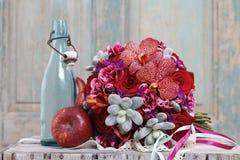 Bouquet avec les fleurs, les roses et les succulents rouges d'orchidée Image stock
