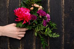 Bouquet of beautiful flowers for the holiday in a female hand on a wooden background stock photos