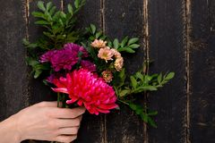 Bouquet of beautiful flowers for the holiday in a female hand on a wooden background stock images