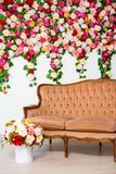 Bouquet of beautiful flowers and vintage sofa over colorful flowers background stock photos